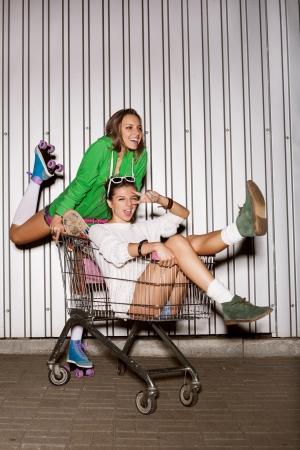 woman shopping cart: Happy two naughty women with shopping cart. outdoors Stock Photo