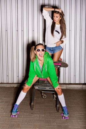 Happy two naughty girls with shopping cart. outdoors photo