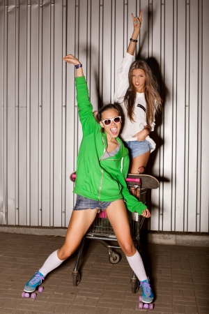 Poartrait of two naughty girls with shopping cart. outdoors photo