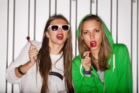 Portrait of two young naughty girls sucking lollipops, outdoors Stock Photo - 15896169