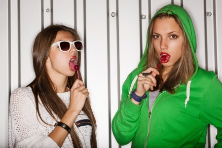 Portrait of two young naughty girls sucking lollipops, outdoors Stock Photo - 15896168