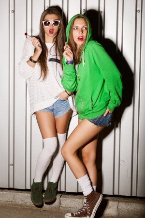 Portrait of two young good looking girls sucking lollipops, outdoors
