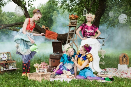 fairy forest: Portrait of four romantic women on a picnic in a fairy forest. Outdoors.