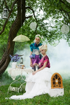 fantasy makeup: Two beautiful romantic women on a picnic in a fairy foggy  forest. Outdoors.