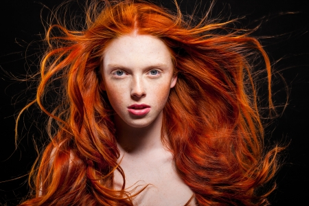 Golden Fashion Girl Portrait.Wavy Red Hair. Black Background