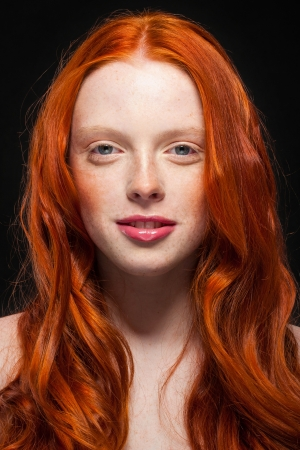 young girl with wavy red hair shows joy. black background photo