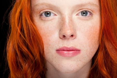 young girl with wavy red hair on black background photo