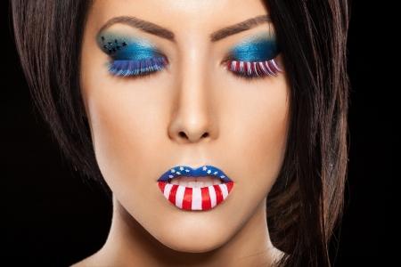 labios sexy: Mujer hermosa cara con maquillaje perfecto en backround negro. en los labios y los ojos pintados una bandera estadounidense