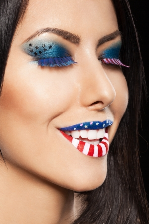 Woman beautiful face with perfect makeup. on the lips and eyes painted an American flag photo