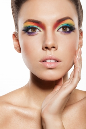 beautiful female face with rainbow makeup. girl touch her face by hand photo