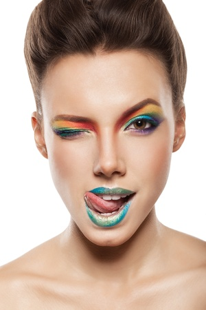 beautiful female face with rainbow makeup. girl winking and showing tongue Stock Photo - 17009370