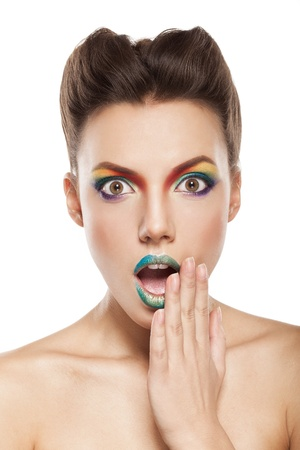 beautiful female face with rainbow makeup. bewildered girl touching her face by hand Stock Photo - 17009292