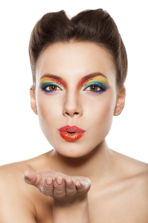 woman blowing: beautiful female face with rainbow makeup, girl blowing a kiss