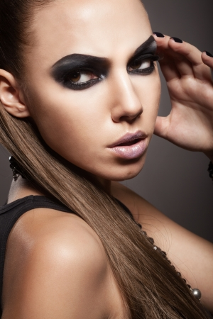 Sexy woman with long hair, make-up and smokey eyes photo