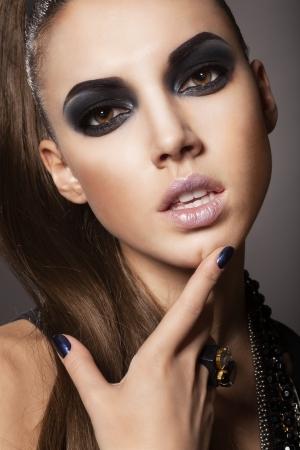 Sexy woman with long hair, make-up and smokey eyes