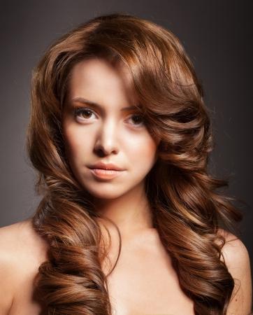 bello rostro femenino con maquillaje y el pelo rizado y brillante. Elegante peinado para cabello largo Foto de archivo - 17383317