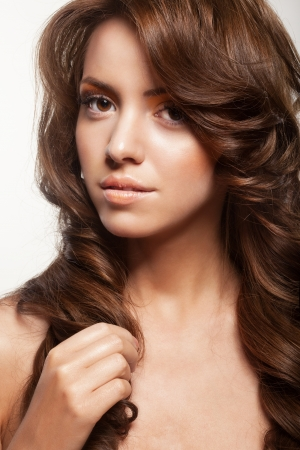 natural looking: beautiful female face with make-up and shiny curly hair. Elegant hairstyle for long hair
