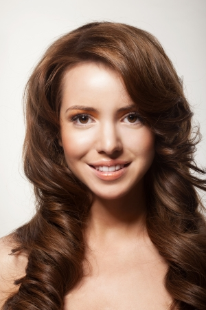 beautiful female face with make-up and shiny curly hair. Elegant hairstyle for long hair photo