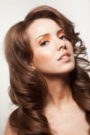 beautiful female face with make-up and shiny curly hair. Elegant hairstyle for long hair Stock Photo - 17383319