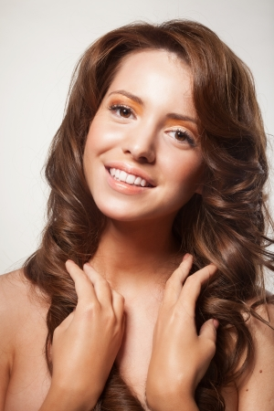 hairdo: beautiful female face with make-up and shiny curly hair. Elegant hairstyle for long hair