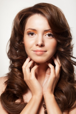 beautiful female face with make-up and shiny curly hair. Elegant hairstyle for long hair Stock Photo - 17383316