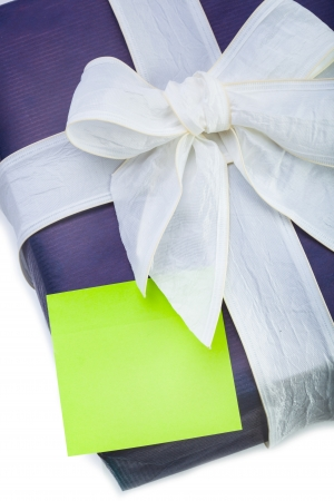 Blue gift box with white ribbon and green note on white background photo