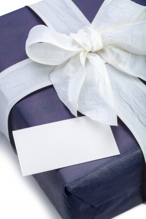 Blue gift box with white ribbon and note on white background photo