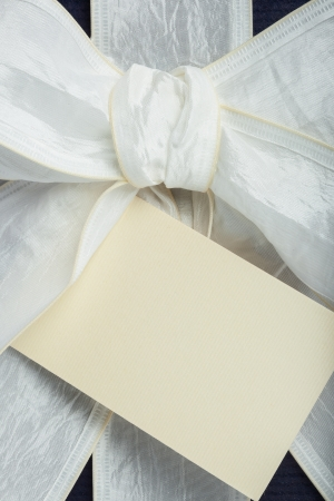 Blue gift box with white ribbon and beige note photo