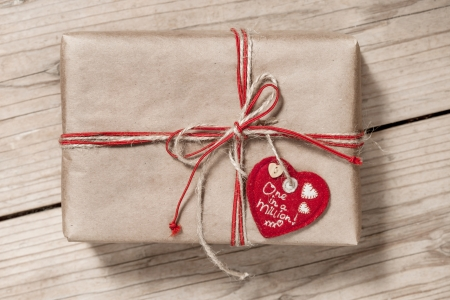 paper gift box with red bow and heart symbol on wooden background photo