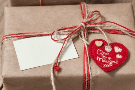 paper gift box with red bow and paper note on wooden background photo
