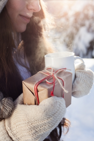 oman drinking tea and holding a gift in hand on a background of a winter landscape, outdoors photo
