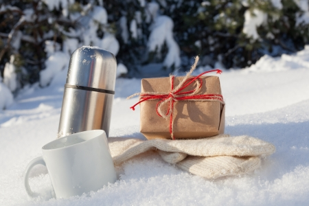 Gift box with cup and mittens in snow on a background of a winter landscape, outdoors photo