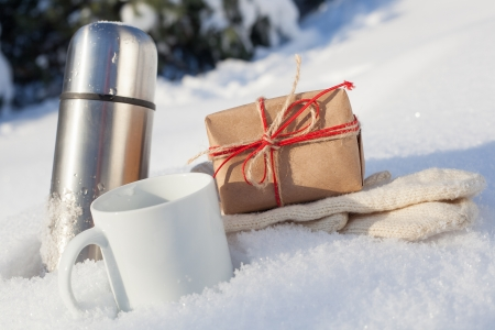 Gift box with cup and mittens in snow on a background of a winter landscape, outdoors