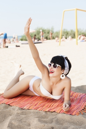 Beautiful sexy young woman relaxing on the beach - outdoors