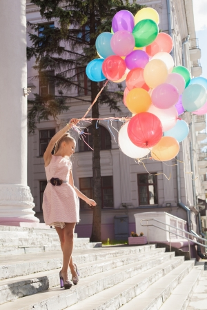 Happy young woman with colorful latex balloons, outdoors photo