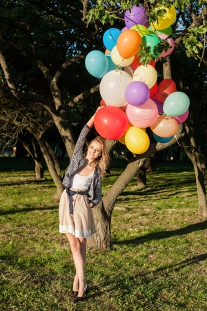latex girl: Happy young woman with colorful latex balloons, outdoors