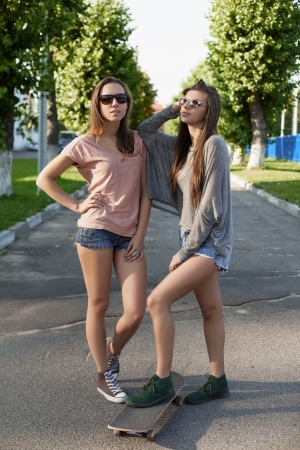 Portrait of girls with a skateboard, outdoors photo