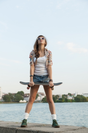 A beautiful skater woman during the sunset, outdoor photo