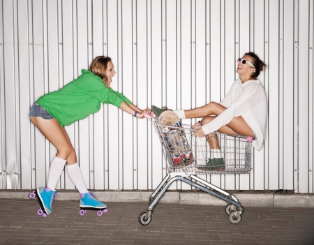 derby: Happy two naughty women with shopping cart  outdoors