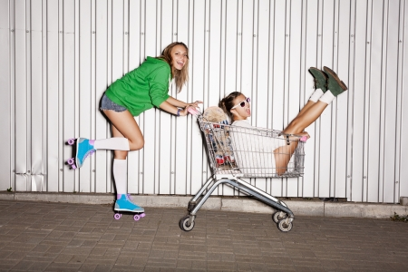 woman shopping cart: Happy two naughty women with shopping cart  outdoors