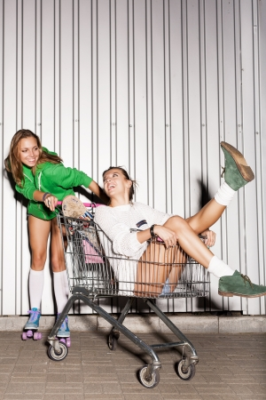 crazy woman: Happy two naughty women with shopping cart  outdoors