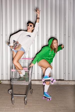 loco: Dos mujeres traviesas felices con el carro de compras al aire libre