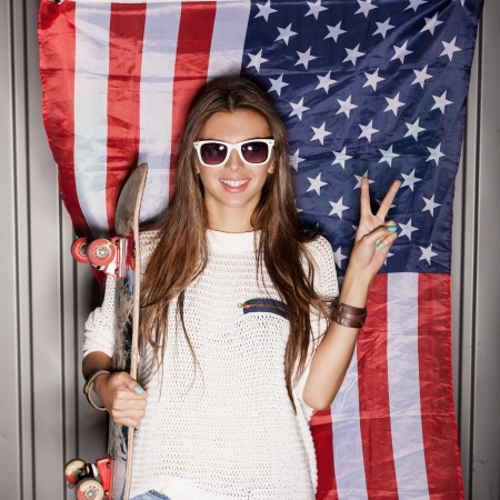 state of mood: beautiful young brunette woman in style cloth and sunglasses with national usa flag in background, 4th july concept