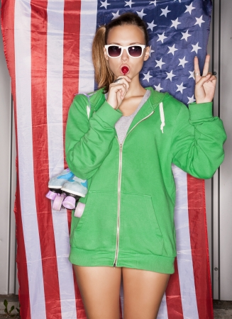 state of mood: beautiful young pretty woman in sunglasses with national usa flag in background, sucking a lollipop