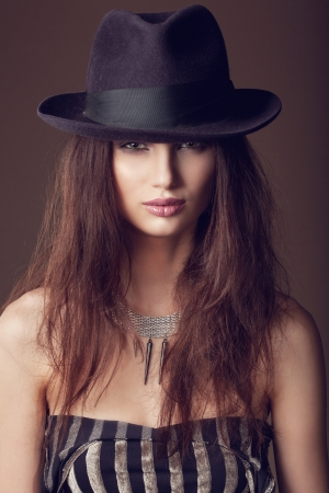 Woman with open lips in hat on dark background, indoor photo