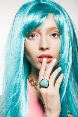 young woman in a bright turquoise wig, indoor photo