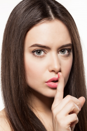finger to lips: Young woman with clean fresh skin ang long hair making a hush gesture, on white background