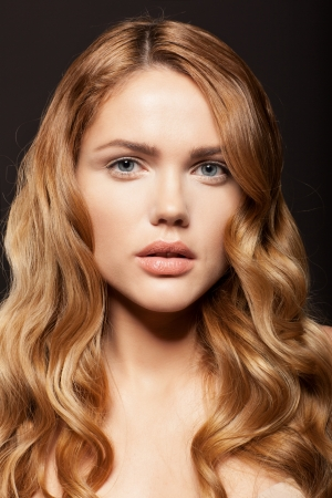 curls: Beauty face of woman with clean fresh skin ang long golden hair on dark background