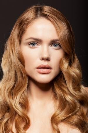 Schoonheid gezicht van vrouw met schone huid ang lange gouden haren op donkere achtergrond