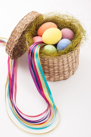 color eggs in wicker basket for holiday easter on white background photo